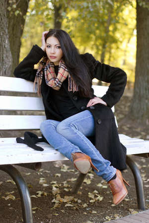 Beautiful young brunette sitting on a bench in autumn park photo
