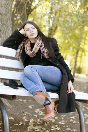 women in jeans: Dreamy young brunette sitting on a bench in autumn park