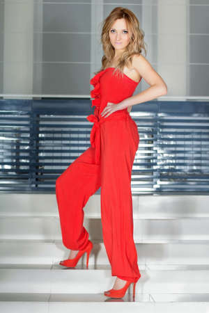 Young woman in a red pantsuit stands on the stairs photo