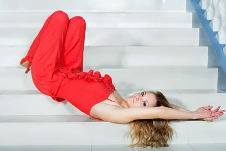 pantsuit: Pretty young woman in a red pantsuit lying on the stairs Stock Photo