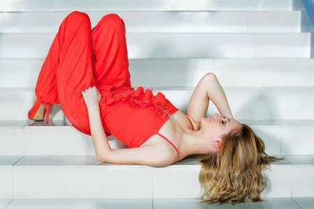 pantsuit: Cute young woman in a red pantsuit lying on the stairs