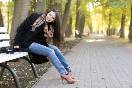 women in jeans: Smiling young brunette sitting on a bench in autumn park