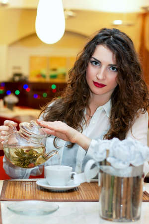 pours: Attractive young woman pours tea into a cup Stock Photo