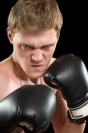 Furious young man in boxing gloves. Isolated on black Stock Photo - 17538902