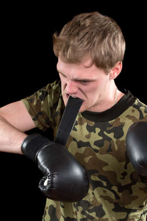 Furious young man in boxing gloves. Isolated Stock Photo - 17538900
