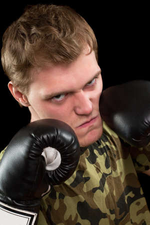Angry young man in boxing gloves. Isolated on black Stock Photo - 17538895