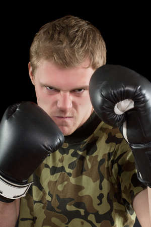 Portrait of furious young man in boxing gloves. Isolated Stock Photo - 17538892
