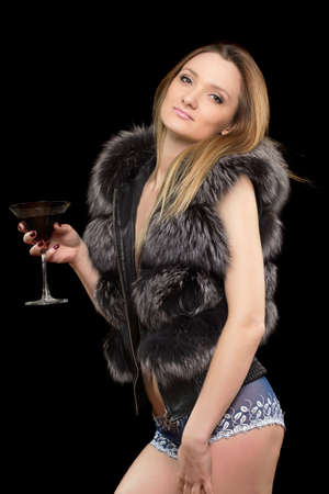 Portrait of young blonde with a glass in hands. Isolated on black photo