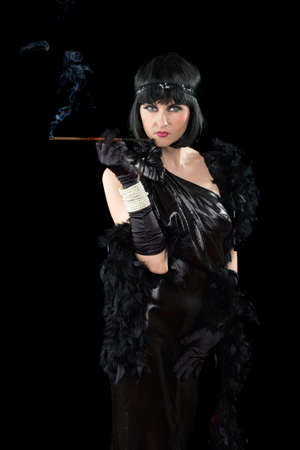 Portrait of young brunette with a cigarette holder dressed in retro style photo
