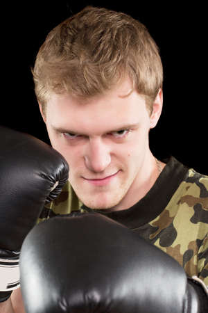 Portrait of grinning angry young man in boxing gloves. Isolated Stock Photo - 17793644