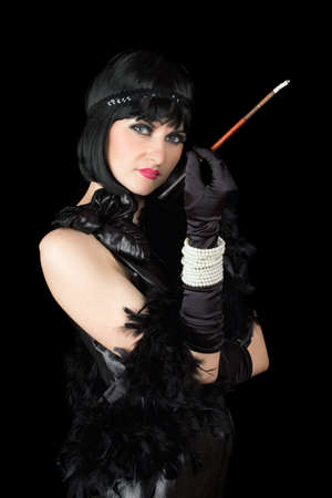 Portrait of brunette with a cigarette holder dressed in retro style photo
