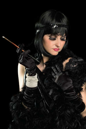 black boa: Portrait of brunette with a cigarette holder dressed in retro style. Isolated