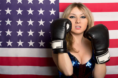 Young blonde with boxing gloves on a background of the American flag photo