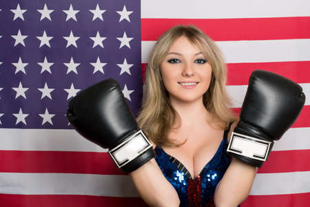 Smiling young blonde with boxing gloves on a background of the American flag photo