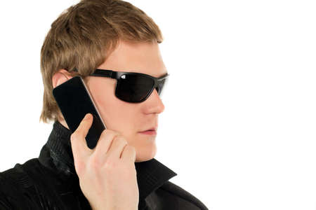 manful: Young man in black sunglasses with mobile phone. Isolated
