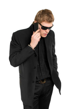 manful: Man wearing black suit and shirt talking on the mobile phone. Isolated Stock Photo