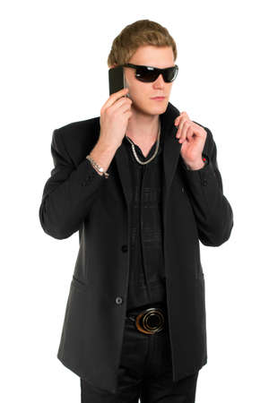 Young man in sunglasses wearing black clothes and talking on the mobile phone. Isolated photo