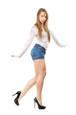 Young woman wearing blue jeans shorts and dancing. Isolated on white photo