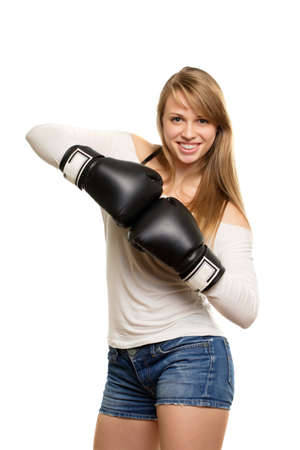 Pretty woman wearing blue jeans shorts and white blouse with black boxing gloves. Isolated  photo