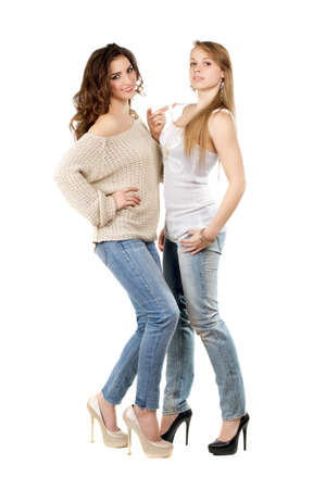 Two pretty women wearing blue jeans and heels. Isolated on white photo