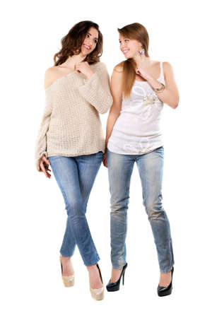 Two joyful women posing in blue jeans and high heels. Isolated on white photo