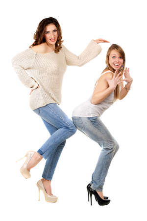 Two playful women wearing blue jeans and high heels. Isolated on white photo