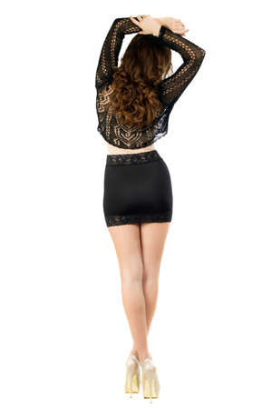 Slim brunette in black skirt and blouse posing back. Isolated on white photo