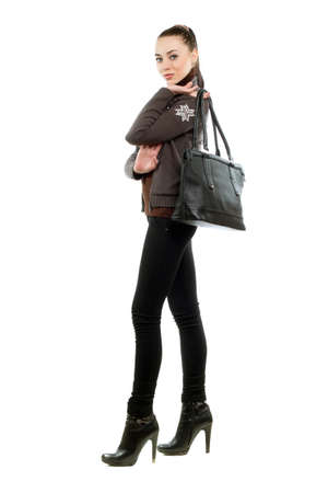 Pretty brunette with a bag wearing black pants and shoes. Isolated on white  photo