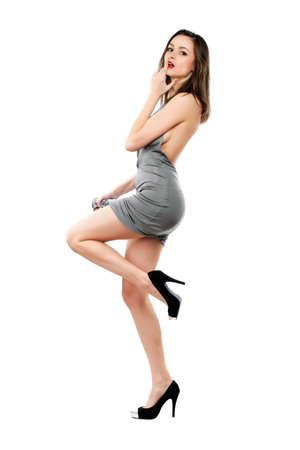morena sexy: Juguet�n Morena sexy con un vestido gris y zapatos negros. Aislados en blanco