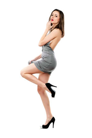 leggy girl: Playful sexy brunette wearing grey dress and black shoes. Isolated on white Stock Photo