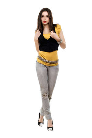 Seductive brunette wearing grey jeans, yellow t-short and black vest. Isolated on white photo