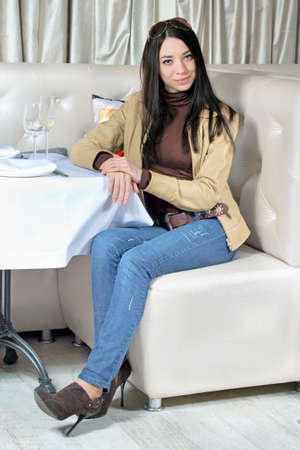 Stylish smiling woman posing in a cozy restaurant. Isolated on white photo