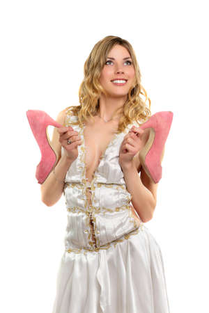 frank: Smiling blonde in frank white dress holding pink shoes. Isolated