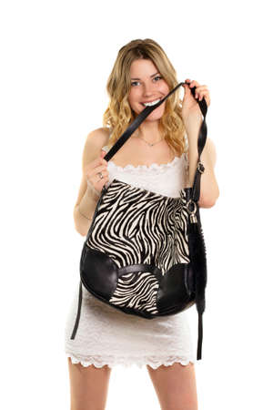Playful blonde biting the strap of her black and white bag. Isolated photo