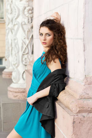Cute brunette in blue dress posing near the building photo