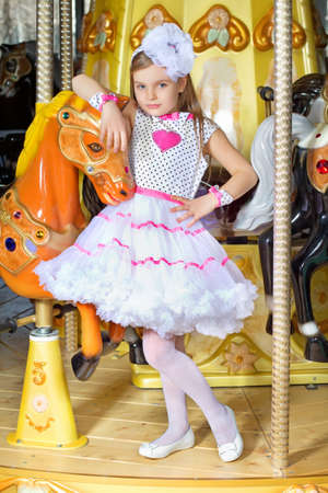 Little beautiful girl in pink and white dress leaning on a carousel pony photo