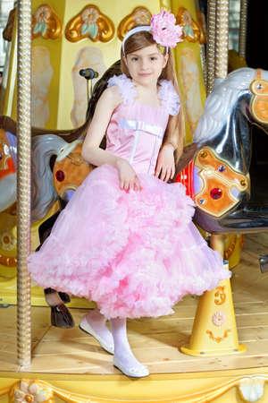 Elegant little girl in beautiful pink dress posing on the carousel Фото со стока