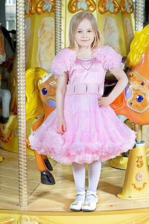 Pretty blond girl in nice pink dress posing on the carousel photo
