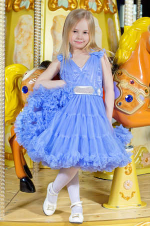 Adorable little girl in blue dress posing near the carousel pony photo