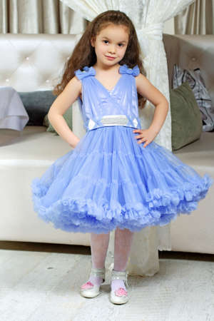 Pretty little girl wearing lace blue dress posing indoors