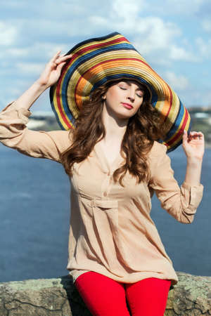 Young brunette in colorful hat sitting on a rock by the river with closed eyes photo
