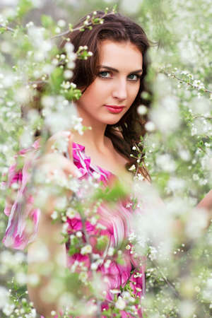 Portrait of pretty young brunette posing in flowering trees photo