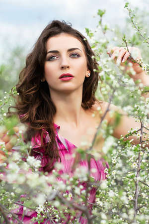 Thoughtful young curly brunette posing in flowering trees photo