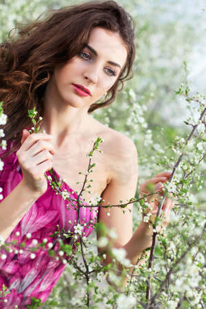 Pretty curly brunette touching the branch of flowering tree photo