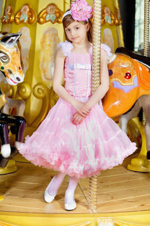 Pretty little girl in pink lace dress standing on the carousel photo