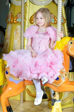 Cute little blond girl in pink dress posing on a carousel pony photo