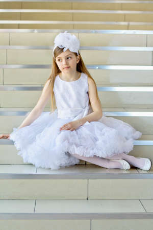 Little girl in white dress, shoes and tights posing on the steps