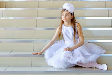 Little thoughtful girl in white dress sitting on the steps