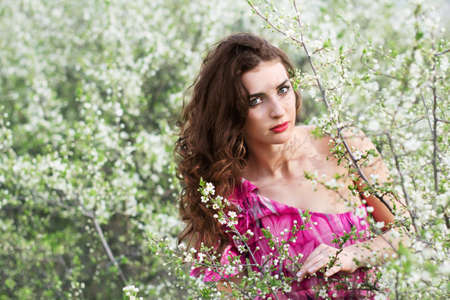 Beautiful brunette wearing pink dress posing in flowering trees  photo