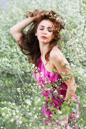 Curly brunette playing with her hair and posing in flowering trees photo